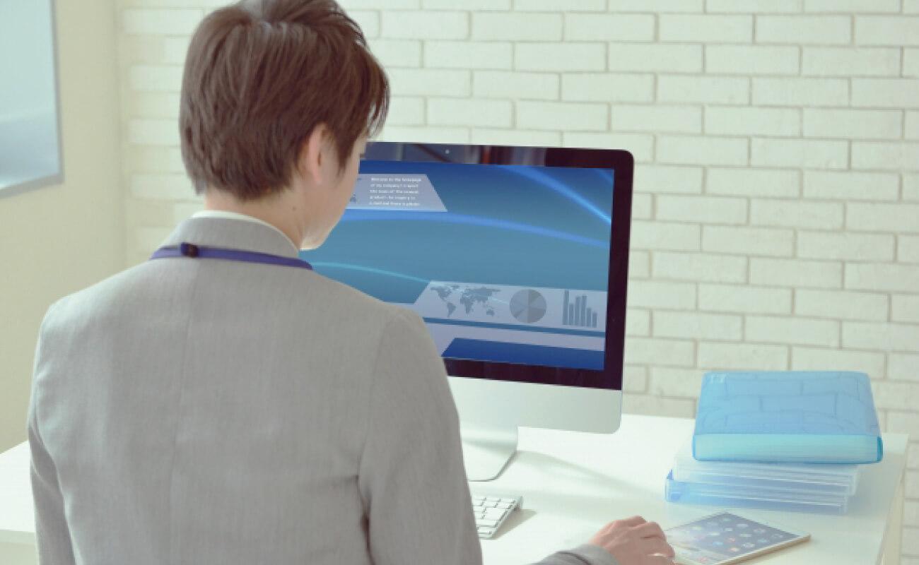 デスクトップPCの前に座る男性の写真